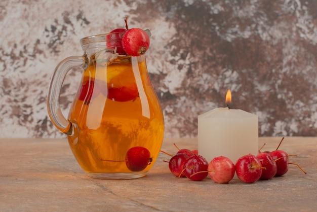 Słoik soku brzoskwiniowego z wiśniami i świecą na marmurowym stole.
