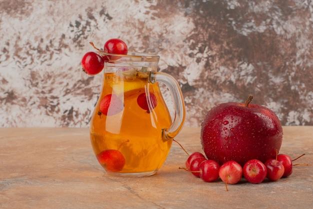 Słoik soku ozdobiony wiśniami i jabłkiem na marmurowym stole.