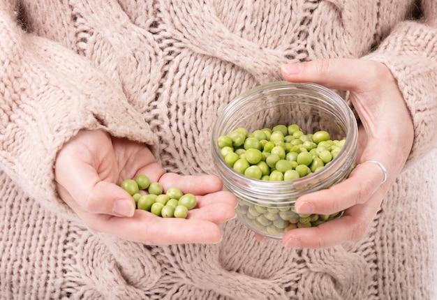 Słoik surowego groszku w rękach kobiety w swetrze