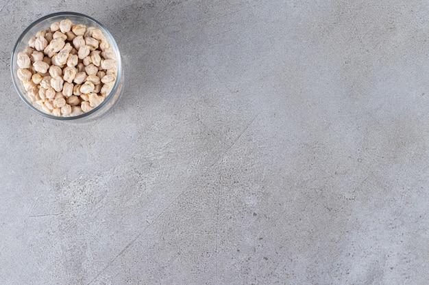 Słoik surowej organicznej ciecierzycy na kamiennym tle.