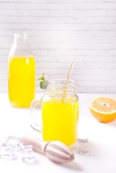 Słoik świeżej lemoniady. pokrojona cytryna na tle.