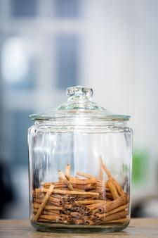 Słoik z aromatycznymi paluszkami cynamonu w szklanej butelce