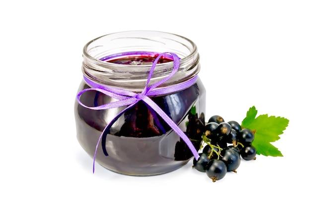 Słoik z dżemem z czarnej porzeczki, gałązki z jagodami i liśćmi czarnej porzeczki na białym tle