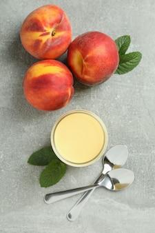 Słoik z jogurtem brzoskwiniowym, brzoskwiniami i łyżkami na szarym tle