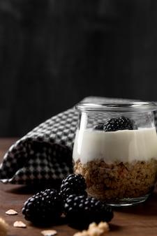 Słoik z jogurtem, muesli i jagodami