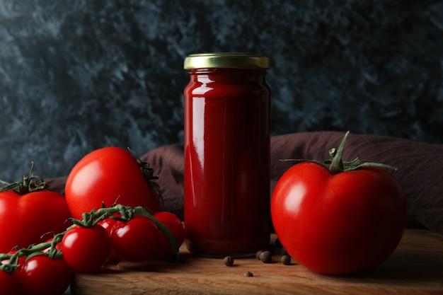 Słoik z koncentratem pomidorowym i pomidorami na drewnianym stole