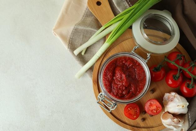 Słoik z koncentratem pomidorowym i składnikami na białym stole z teksturą