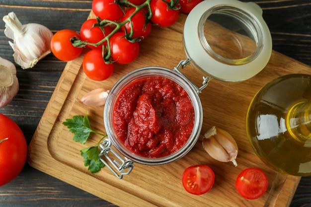 Słoik z koncentratem pomidorowym na drewnianym stole ze składnikami