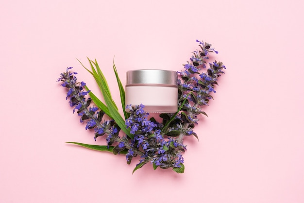 Słoik z kremem do twarzy lub ciała na różowym tle z dzikimi kwiatami i roślinami