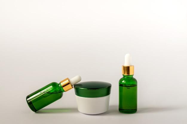 Słoik z kremem nawilżającym, serum w szklanej butelce na białej powierzchni