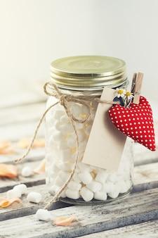 Słoik z marshmallows i serce zaczepione za pomocą kleszczy