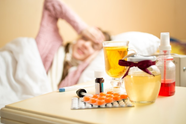 Słoik z miodem, filiżanką herbaty i lekarstwami leżącymi na stole obok łóżka chorej dziewczynki