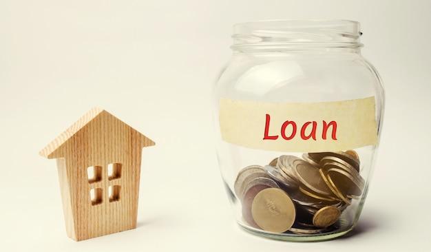 Słoik z napisem pożyczka i mały drewniany dom. kupno domu w długach.