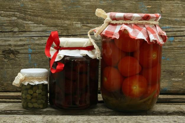 Słoik z przetworami. domowy dżem truskawkowy, marynowane pomidory i kapary na podłoże drewniane
