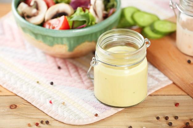 Słoik z smacznym sosem do sałatki na stole