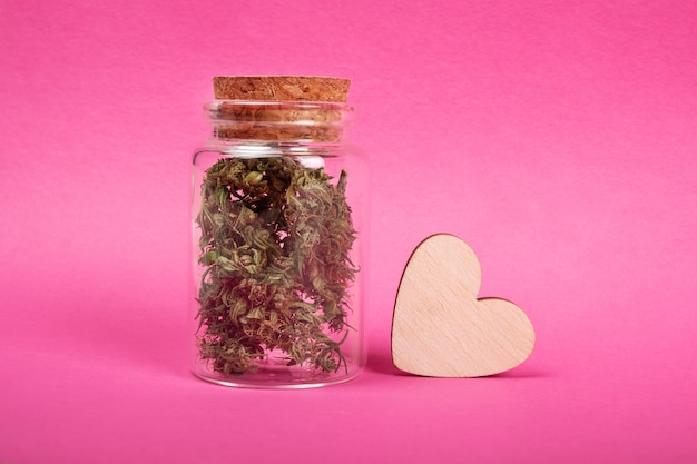 Słoik z symbolem miłości do marihuany z suchymi pąkami konopi i drewnianym sercem na różowym tle