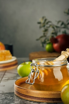 Słoik ze świeżym miodem, łyżką miodu, jabłkiem i granatem. koncepcja żydowskiego nowego roku szczęśliwego święta rosz haszana. układ tradycyjnych symboli. widok z góry. shana tova