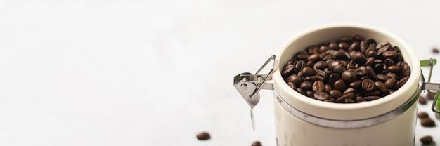 Słoik ze świeżymi ziarnami kawy i ziarna kawy są rozrzucone na betonowym tle.