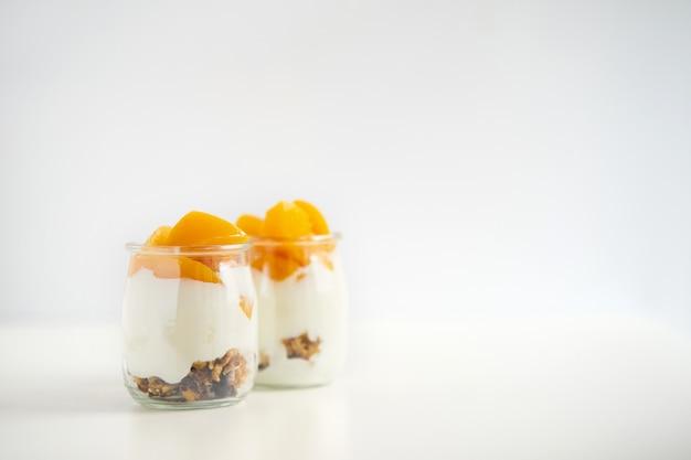Słoiki greckiego jogurtu z muesli i morelami w puszkach