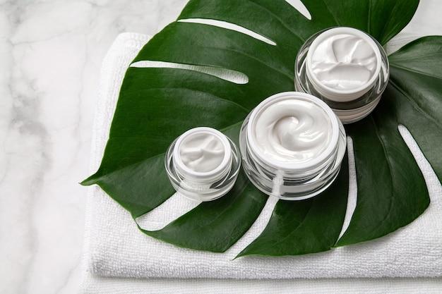 Słoiki kosmetyczne kontenerowe krem z ręcznikiem i zielonym liściem na tle marmuru.