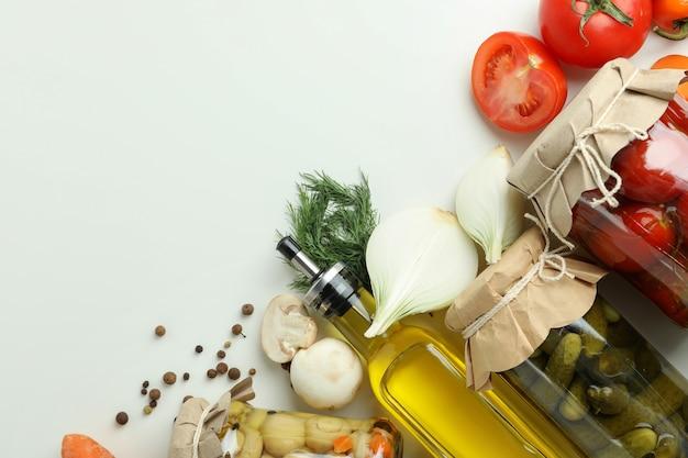 Słoiki marynowanych warzyw i składników na białym stole