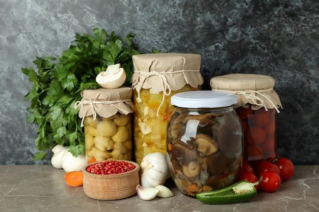 Słoiki marynowanych warzyw i składników na szarym teksturowanym stole