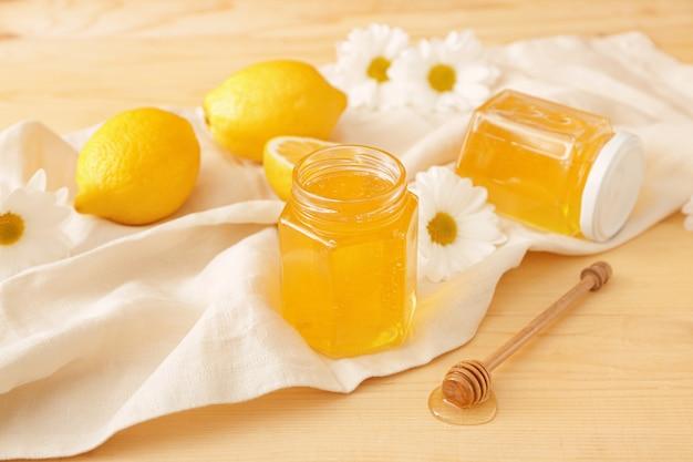 Słoiki słodkiego miodu i cytryn na stole