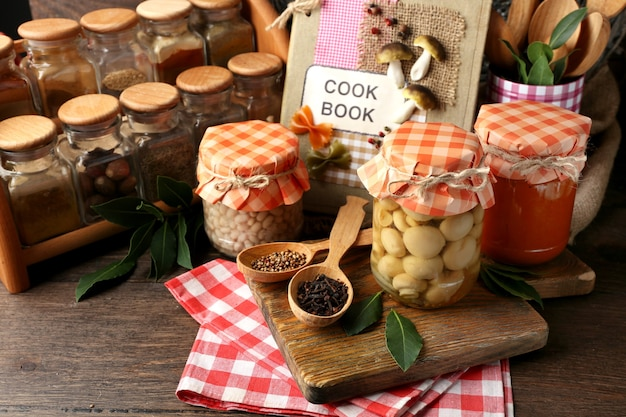 Słoiki z marynowanymi warzywami i fasolą, przyprawy, księga przepisów i naczynia kuchenne na drewnianym tle