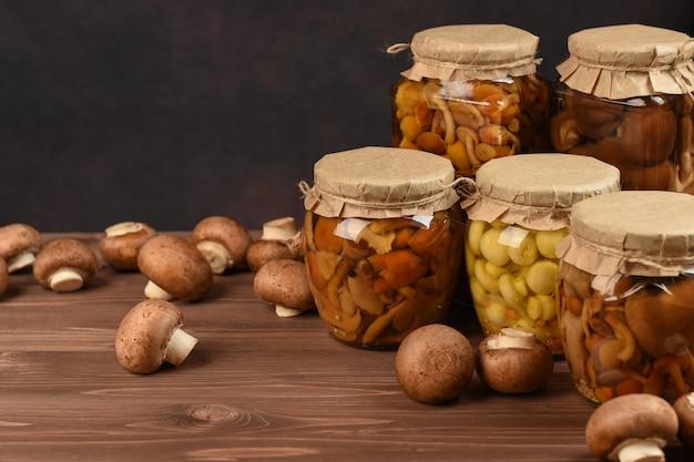 Słoiki z różnymi grzybami. marynowane grzyby w puszkach w szklanych słoikach. utrzymane pieczarki na drewnianym stole.