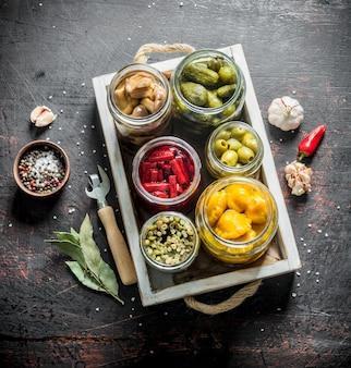 Słoiki z różnymi konserwami warzywnymi na tacy. na ciemny rustykalny