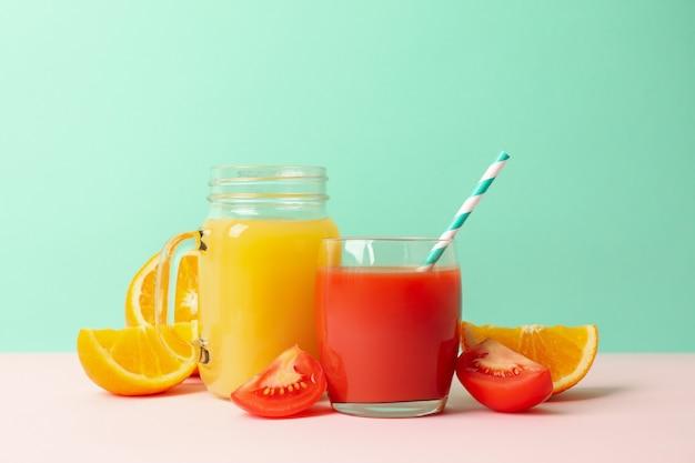 Słoiki z sokiem pomidorowym i pomarańczowym na tle mięty