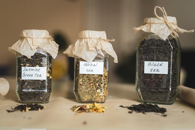 Słoiki z trzema rodzajami herbaty na stole, alternatywnymi lekami i naturalnym jedzeniem.