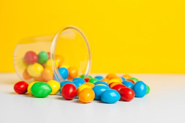Słoiki ze słodkimi cukierkami na stole