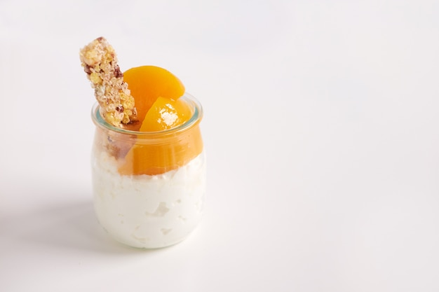 Słój jogurt lub twaróg z granola i konserwować morelami na białym tle, zamyka