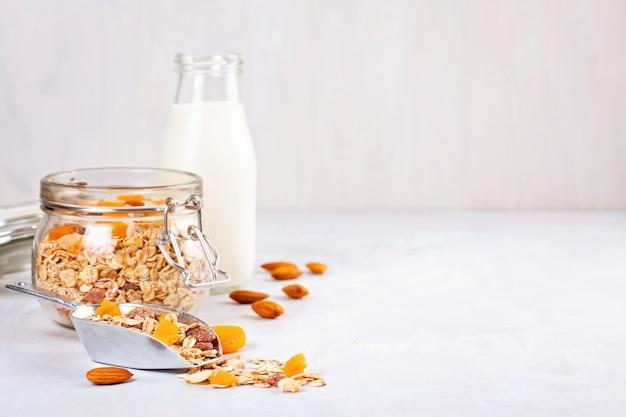 Słój z domowej roboty muesli z orzechami i suszonymi owocami i mlekiem migdałowym. zdrowe śniadanie dietetyczne
