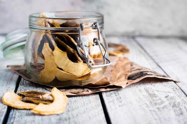 Słój z jabłczanymi i bananowymi układami scalonymi na drewnianym stołowym tle.