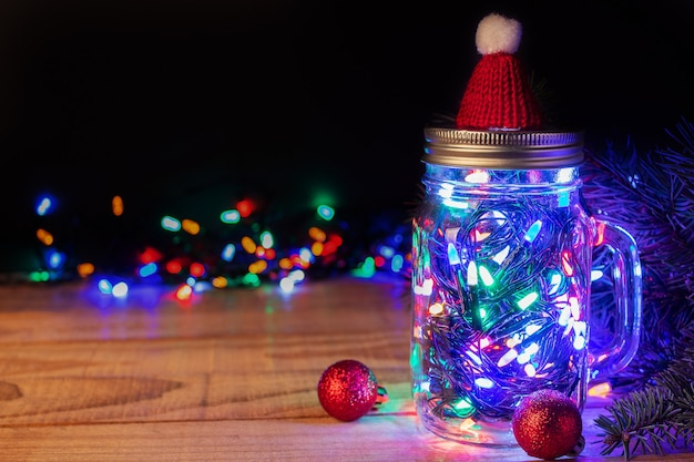 Słój z kolorowymi świątecznymi lampkami na rustykalnym drewnianym stole na ciemnym tle, miejsce na tekst. świętujemy boże narodzenie i nowy rok