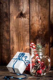 Słój z ozdób choinkowych, szyszek jodły, sztucznego śniegu, trzciny cukrowej i gałęzi jodły