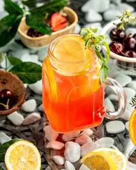 Słój z pomarańczowym koktajlem z pomarańczowymi plasterkami