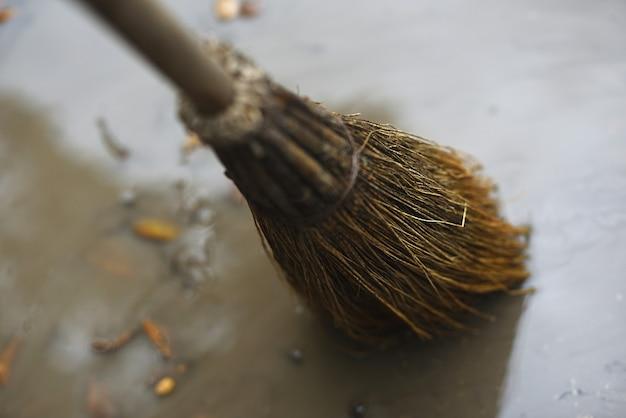 Słomiana miotła zamiata kałużę deszczu