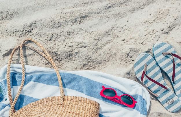 Słomiana torba, okulary przeciwsłoneczne i klapki na tropikalnej piaszczystej plaży