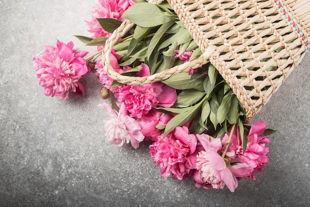 Słomiana torba z różową peonią kwitnie na szarym tle.