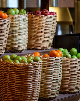 Słomiane kosze z owocami wypełnione jabłkami, granatami i pomarańczami