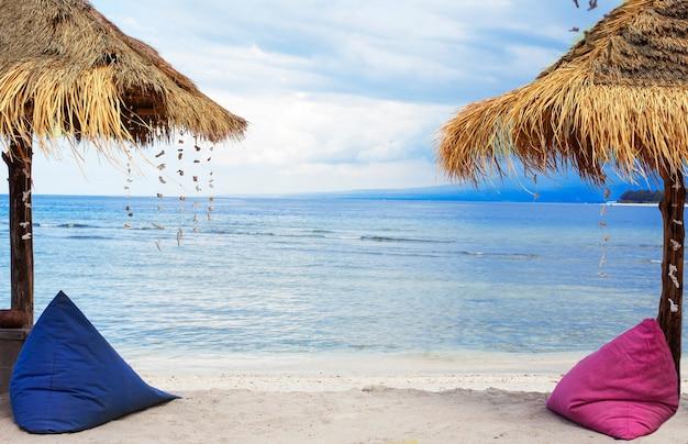 Słomiane parasole i worek fasoli nad brzegiem morza.