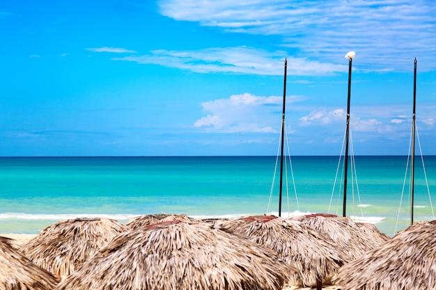 Słomiane parasole z żaglówkami na plaży w varadero na kubie.