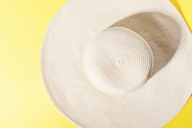 Słomiany kapelusz na jaskrawym żółtym pogodnym tle