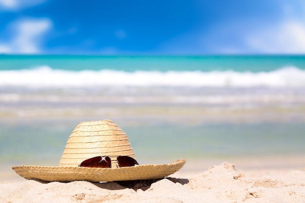 Słomiany kapelusz z okularami przeciwsłonecznymi na białym piasku przeciw turkus wody zadziwiającemu oceanowi i niebieskiemu niebu