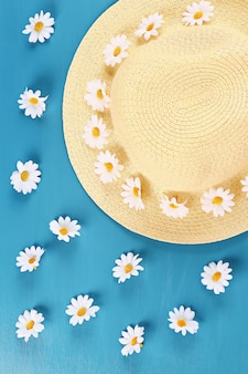 Słomiany kapelusz z rumiankiem na błękitnym tle. widok z góry. tło lato. leżał płasko.