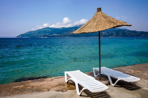 Słomiany parasol i para leżaków na plaży w sarandzie w albanii