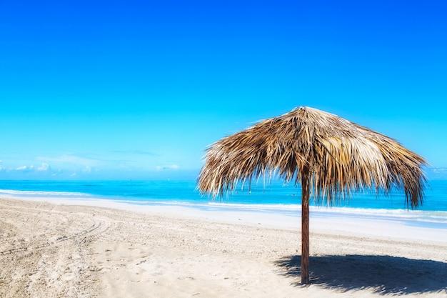 Słomiany parasol na pustej nadmorski plaży w varadero, kuba.